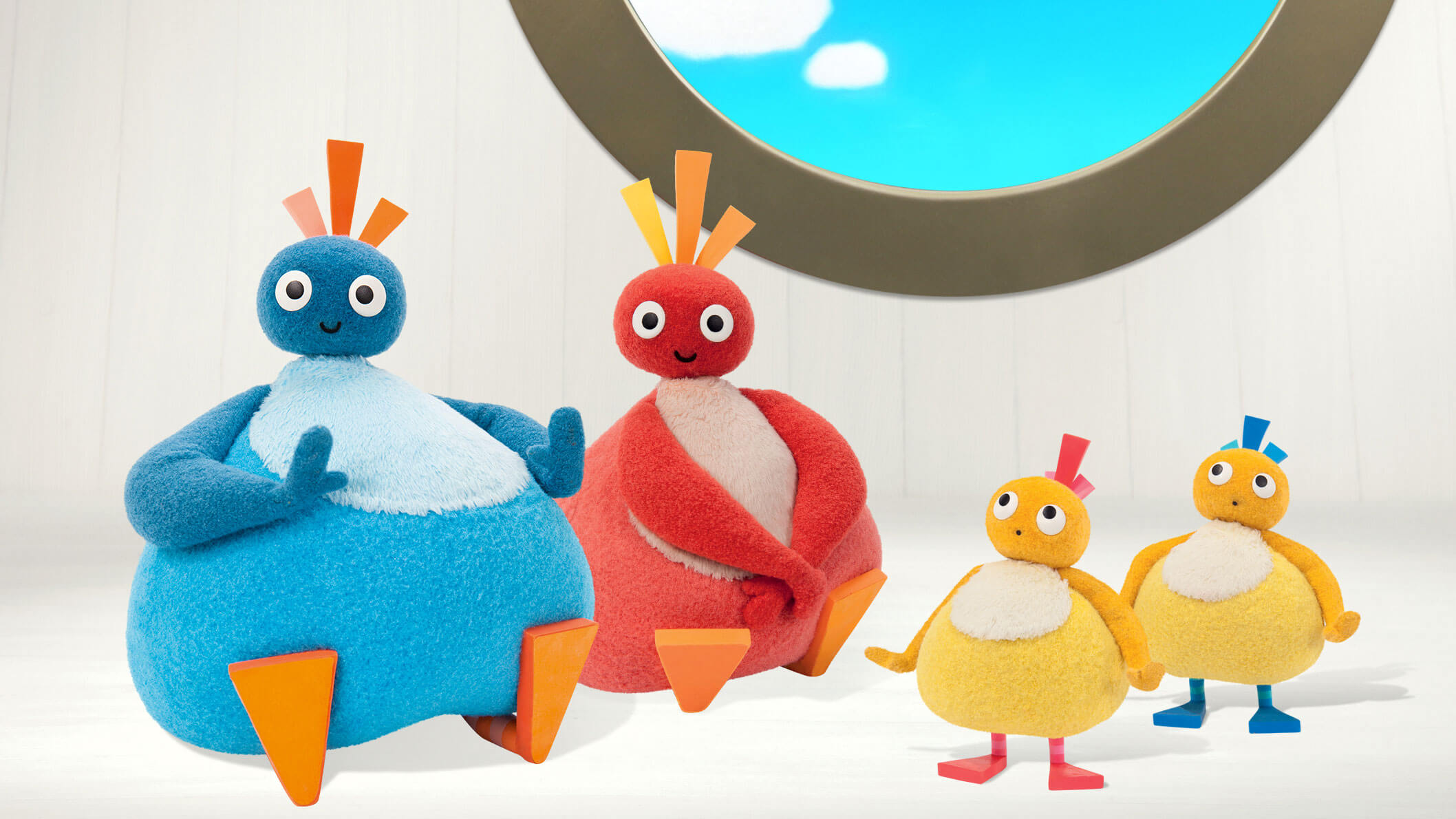 A round, blue character and a red character sitting on the ground in front of a white wall and a round window. There are two small, round and yellow characters standing beside them with a worried look on their face.