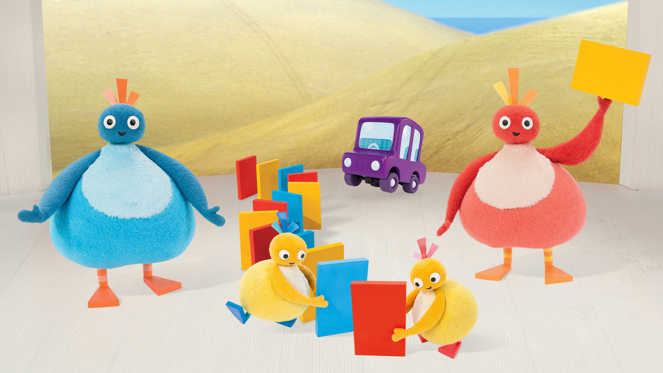 A blue round character, a red round character and two smaller, yellow characters in front of two beige hills and a purple car in the background.