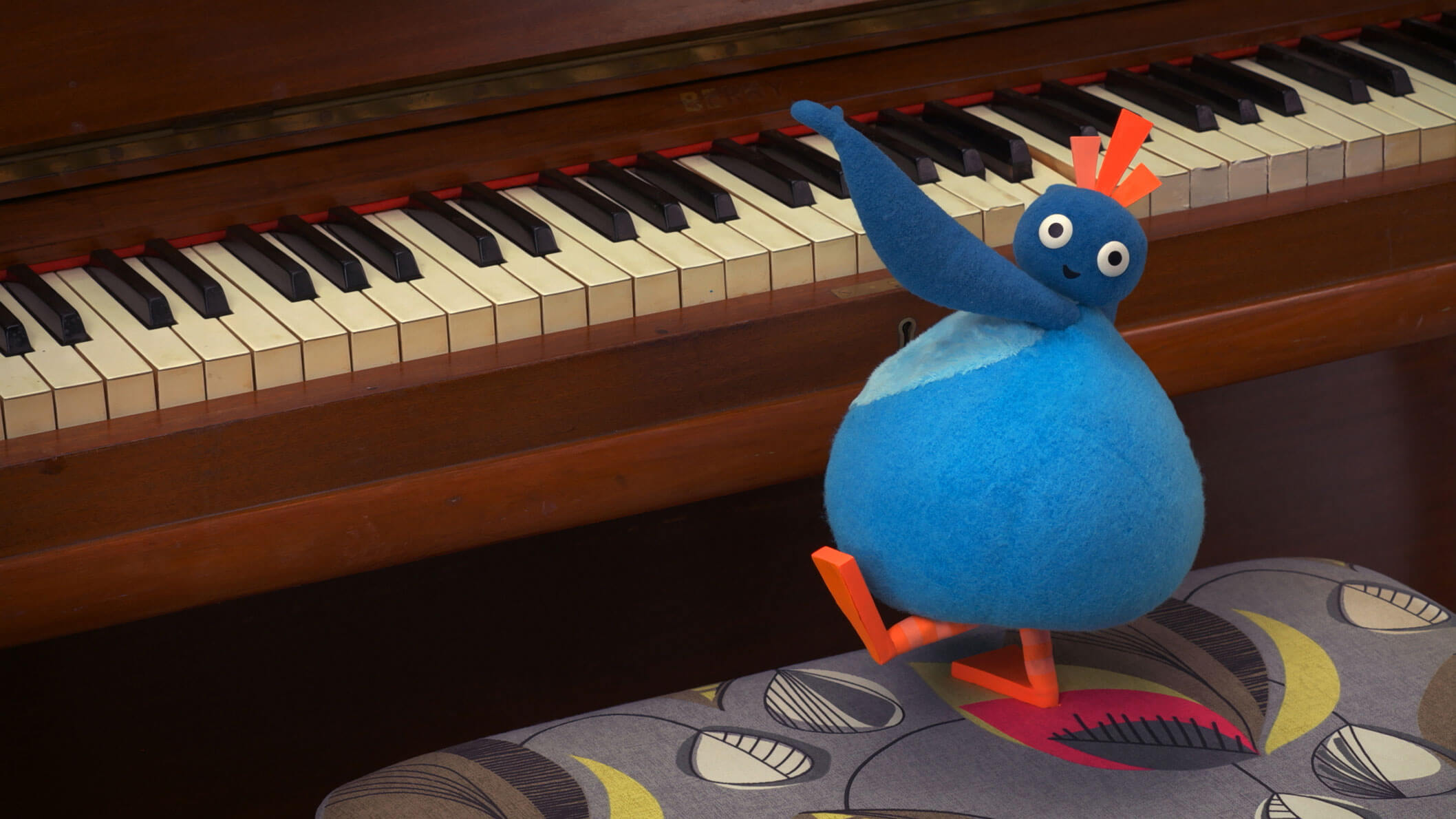 A small, round, blue character playing on a brown piano with it's head turned away from the piano keys.