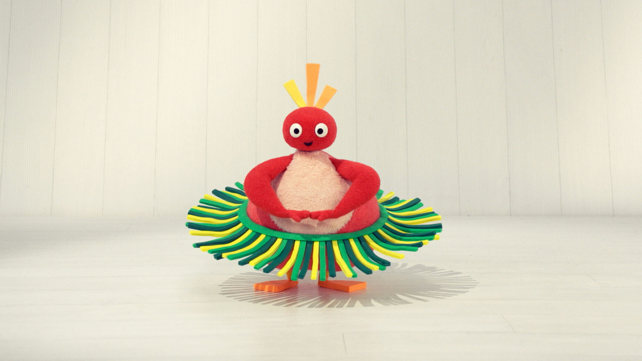 A red character with a pear-shaped body and a round head wearing a green hula skirt in front of a white background.
