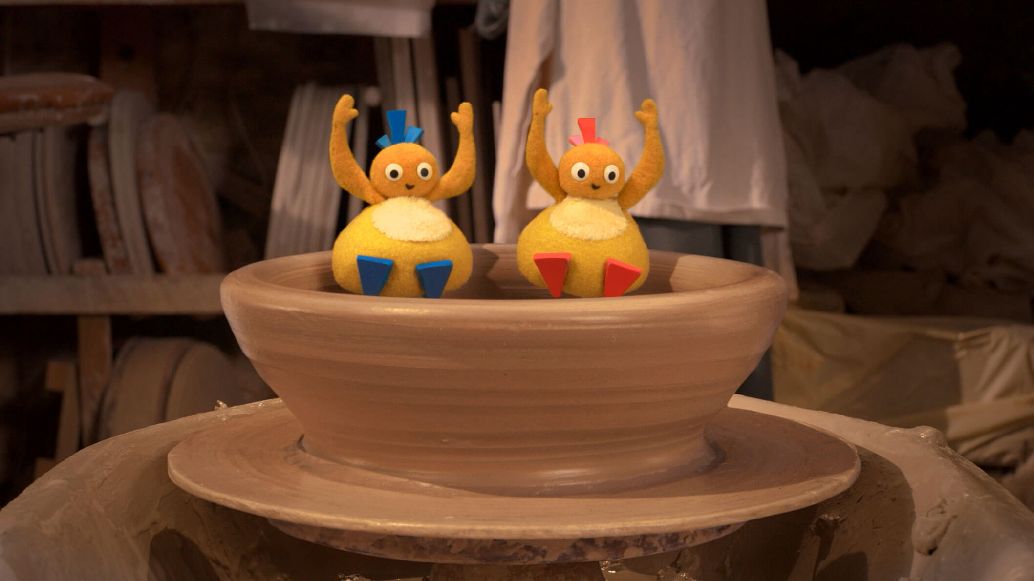 Two small, round and yellow characters sitting in a wed clay bowl waving their hands up in the air.