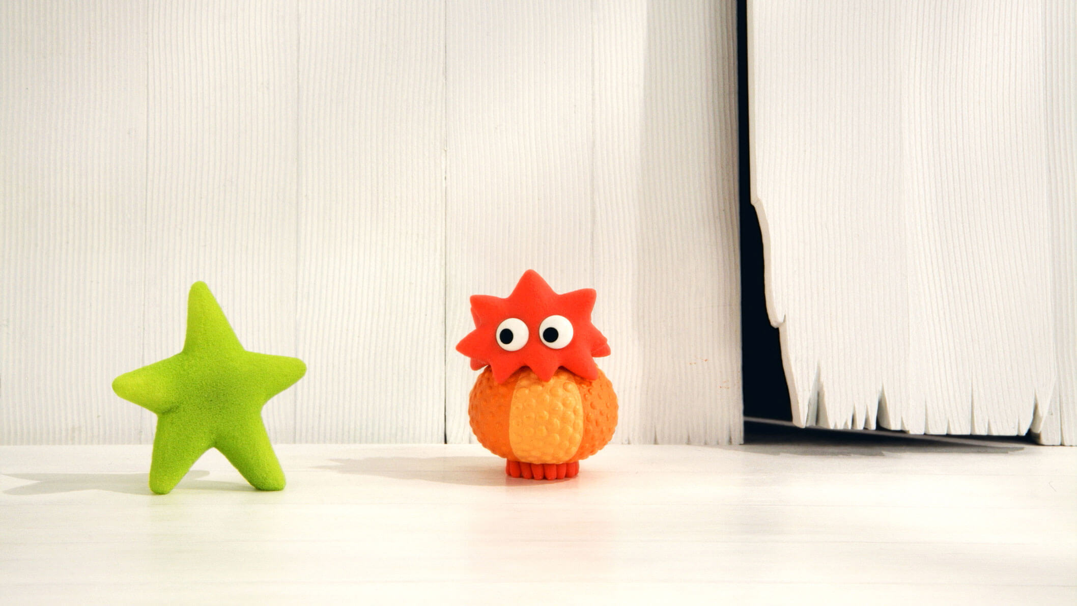 A small red character with a round body and star-shaped head standing in front of a white wall and beside a green star on the left.