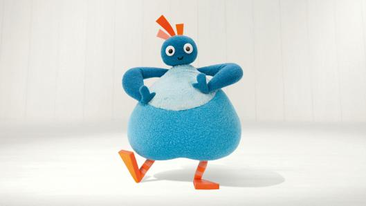 A blue, pear-shaped character with a small round head and orange feet is dancing in front of a white background.