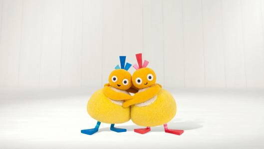 Two small, yellow characters hugging each other in front of a white background. One has blue hair and feet and the other one has red hair and feet.
