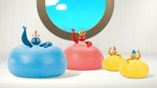 A blue character sitting inside a blue ring, a red character in a red ring, and two small characters sitting inside yellow rings in front of a round window looking out on a blue sky.