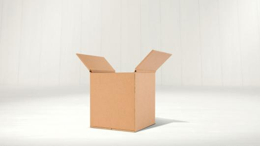 A square, cardboard box sitting on a white surface in front of a white background.