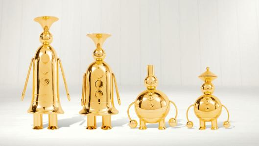 Four gold characters, shaped like instruments standing on a white surface in front of a white wall.