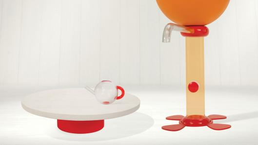 A clear, cylinder shaped tea machine on the right, a red and white table on the left with a red and white teapot on it.