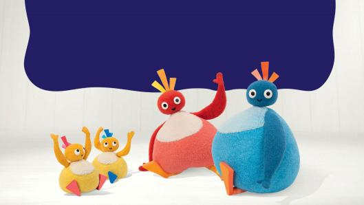 A family of four round characters sitting on the ground waving. From the left, there are two small, yellow character, a red character and a blue character.