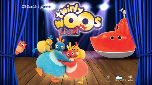 A family of four plush characters, with pear-shaped bodies and small round heads, hugging on a stage with blue curtains. There is a red boat behind them and a logo.