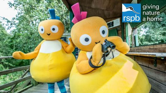 Two yellow characters with small round heads and a pear-shaped body, walking on a wooden boardwalk in a park. One of the characters is holding binoculars.