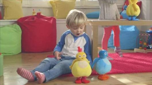 A blonde pre-school boy sitting on the floor in his bedroom looking at his two toys: a yellow, round character and  a blue, round character.
